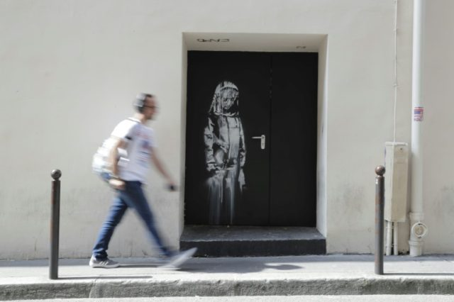 A man walks past an image of a woman apparently in mourning by Banksy on a side street around the corner from the Bataclan concert hall in Paris where jihadists killed 90 people in November 2015