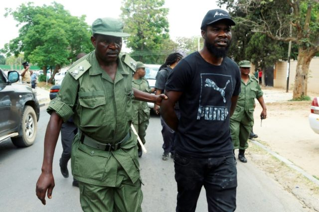 Zambian musician Chama Fumba, known as Pilato, is led away by police after the protest