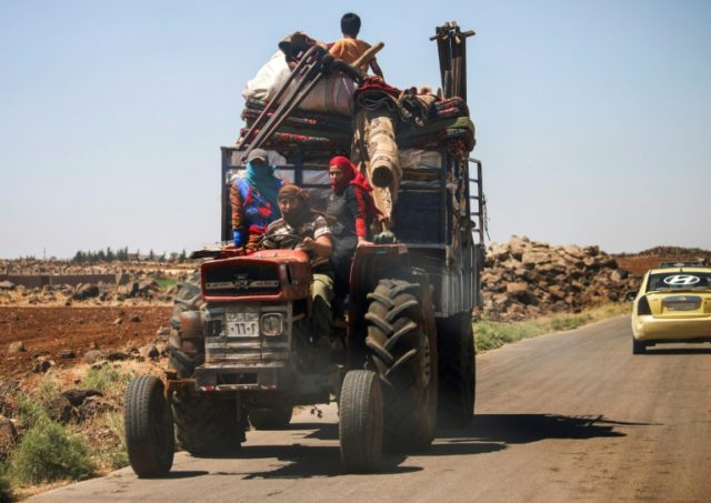 A Syrian family sit in a tractor-drawn trailer packed with their belongings as they flee from fighting in the southern province of Daraa on June 21, 2018