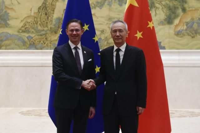 European Commission Vice President Jyrki Katainen (L) shakes hands with Chinese Vice Premier Liu He before their meeting