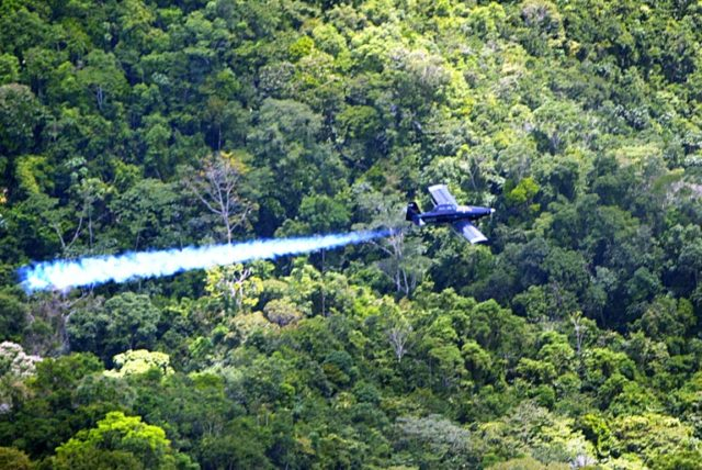 A Colombian police plane sprays herbicides on coca plants in the suburbs of Medellin on July 23, 2003
