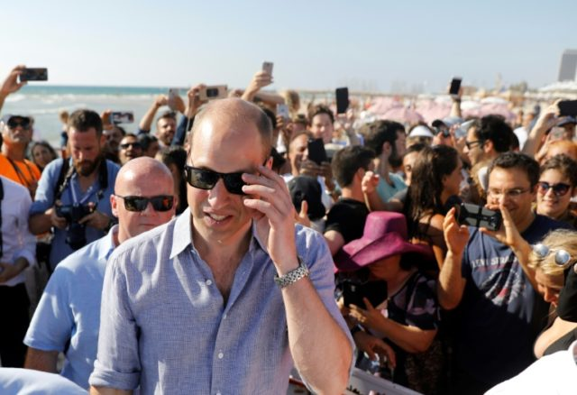 Britain's Prince William (C) adjusts his shades as visits a beach in Tel Aviv on June 26, 2018