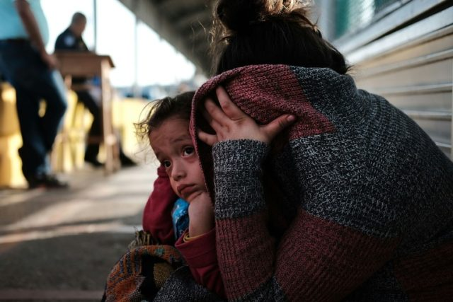 A Honduran child and her mother, fleeing poverty and violence in their home country, wait along a border bridge after being denied entry from Mexico into the US on June 25, 2018 in Brownsville, Texas
