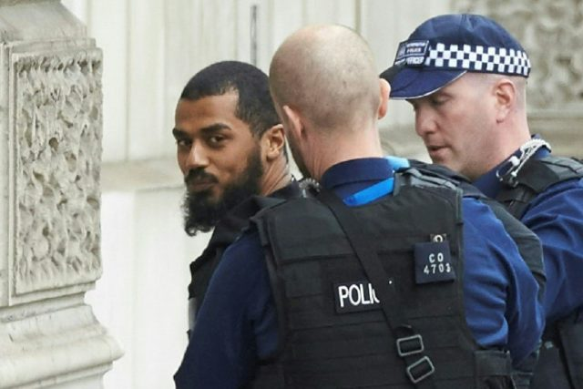 British police detaining Khalid Mohammed Omar Ali near the Houses of Parliament in central London last year. He was found guilty Tuesday of plotting a knife attack on MPs and police
