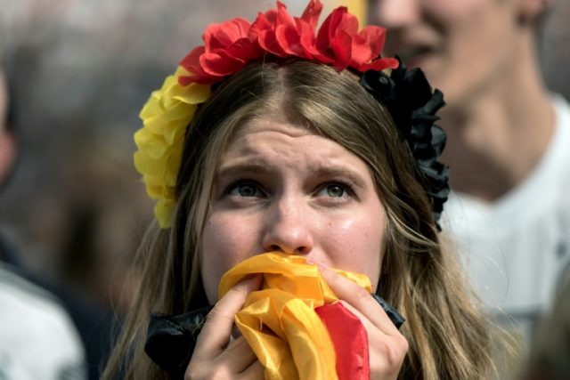 A supporter of the German national football team watching the action on a big screen in Frankfurt reacts with sadness as her team