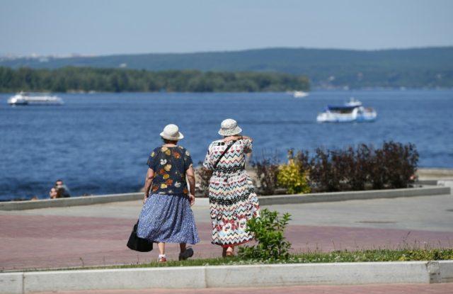 Women walk along the Volga river in Samara, Russia