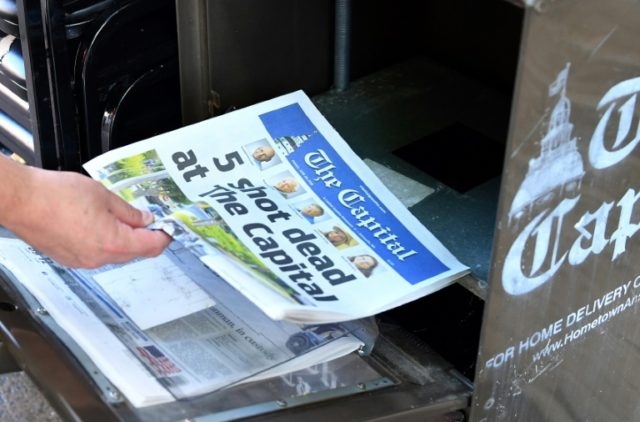 A resident buys The Capital newspaper, published despite a shooting which took the lives of five of its staff a day earlier