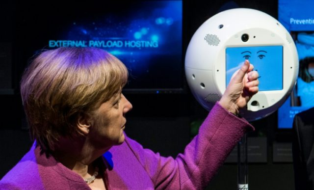 "German Chancellor Angela Merkel interacts with a ""floating brain"" device code-named CIMON -- designed to aid astronauts aboard the International Space Station -- at a Berlin aerospace exhibit in April 2018"