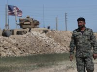 In this April 4, 2018 file photo, a U.S-backed Syrian Manbij Military Council soldier passes a U.S. position near the tense front line with Turkish-backed fighters, in Manbij, north Syria. The People's Protection Units, known by their Kurdish acronym YPG, said in a statement Tuesday, June 5, 2018, that it's …
