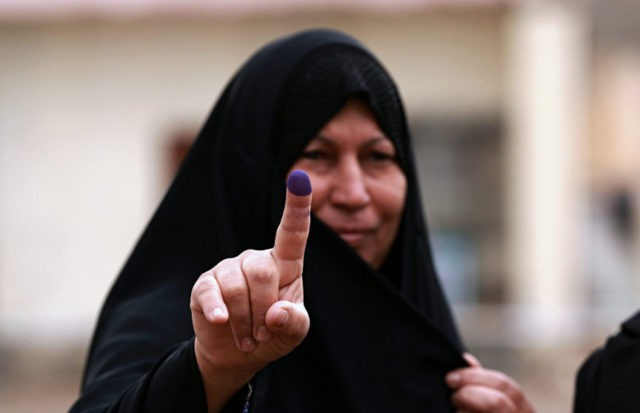 In this May 12, 2018 file photo, an Iraqi woman shows her ink-stained finger after casting her vote in the country's parliamentary elections in Ramadi, Iraq. Iraq's parliament voted on Wednesday, June 6, 2018, in favor of a manual ballot recount after allegations of widespread fraud in the country's recently …