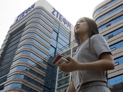 In this May 8, 2018, file photo, a woman passes by a ZTE building in Beijing, China. Chinese tech giant ZTE Corp.'s chairman promised no further compliance violations and apologized to customers in a letter Friday, June 8, 2018, for disruptions caused by its violation of U.S. export controls, a …
