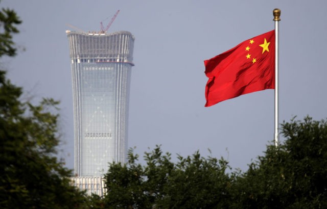 "In this Thursday, June 14, 2018, file photo, a Chinese national flag at Tiananmen Square flutters against the capital city tallest skyscraper China Zun Tower under construction at the Central Business District in Beijing. China has threatened ""comprehensive measures"" in response to U.S. President Donald Trump's new tariff hike, raising …"
