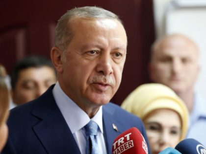 Turkey's President and ruling Justice and Development Party, or AKP, leader Recep Tayyip Erdogan talks to journalists at a polling station for Turkey's elections in Istanbul, Sunday, June 24, 2018. Turkish voters are voting Sunday in a historic double election for the presidency and parliament. (AP Photo/Lefteris Pitarakis)