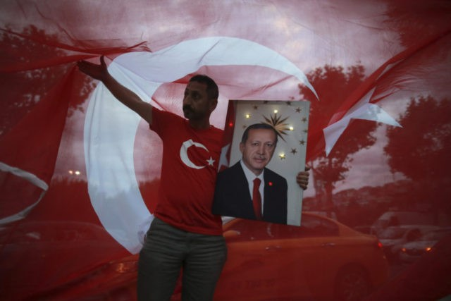 A man hold a picture of Turkey's President and ruling Justice and Development Party, or AKP, leader Recep Tayyip Erdogan while celebrating outside the party headquarters in Istanbul, Sunday, June 24, 2018. Early partial results in Turkey's presidential elections Sunday showed incumbent Recep Tayyip Erdogan in the lead, with challenger …