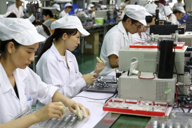 In this June 23, 2018, photo, workers inspect the micro-motors for handsets at a factory in Huaibei in central China's Anhui province. China's government defended its trade record as a benefit to the world in a new effort Thursday, June 28, 2018 to defuse U.S. and European pressure over market …
