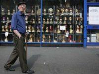 a man walking past a London wig shop