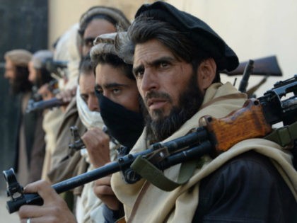 Afghan alleged former Taliban fighters carry their weapons before handing them over as part of a government peace and reconciliation process at a ceremony in Jalalabad on February 24, 2016. More than a dozen former Taliban fighters from Nazyan district of Nangarhar province handed over their weapons as part of …