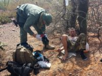 Border Patrol agent assists migrant suffering from dehydration in desert. (AP File Photo: Astrid Galvan)
