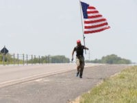 "A Missouri veteran, Elliot Timms, donning a ""Make America Great Again"" hat and brandishing an American flag, has been running 15 miles nearly every day for a year hoping to show everyone how much he loves his country."