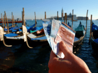 399185 03: A handful of new Euro notes are held in front of a row of Gondolas January 3, 2002 in Venice, Italy. The Euro went into effect on January 1, 2002 in 12 European countries. (Photo By Justin Sullivan/Getty Images)