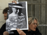 Israeli left wing activists hold posters on January 18, 2016 outside a courthouse in Jerusalem during a demonstration to ask for the release of Ezra Nawi, a Jewish man suspected of informing on Palestinians selling property to settlers, a week after he was arrested. Israeli media said Ezra Nawi was …