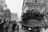Inhabitants of the former Soviet-occupied Polish city of Lwow wave at a passing truckload of German soldiers as Nazi troops take over the city on July 2, 1941, according to the caption passed through German government censors. The city is now known as Lviv in Ukraine. (AP Photo)