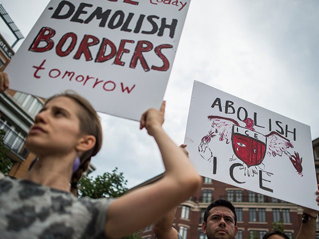 People hold up signs as they protest the US Immigration and Customs Enforcement agency (ICE) and the recent detentions of illegal immigrants in Washington, DC on July 16, 2018. - The coalition of activists called on the government to abolish ICE.