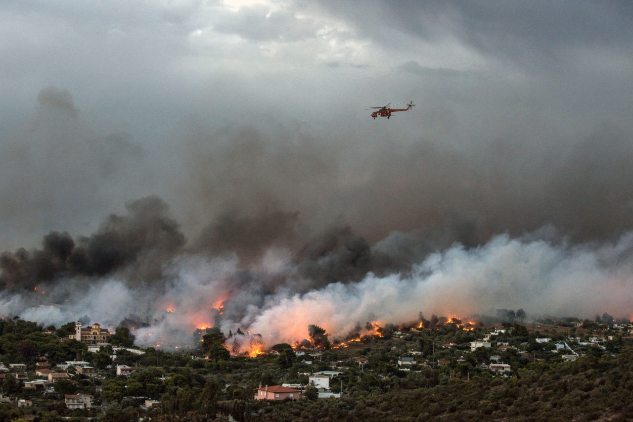 A firefighting helicopter flies over a wildfire raging in the town of Rafina near Athens