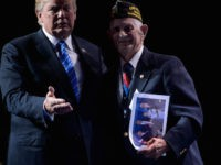 US President Donald Trump walks with WWII veteran Allen Q. Jones after signing a photo for him at the 119th Veterans of Foreign Wars National Convention on July 24, 2018, in Kansas City, Missouri. (Photo by Brendan Smialowski / AFP) (Photo credit should read BRENDAN SMIALOWSKI/AFP/Getty Images)
