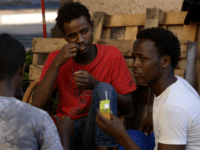 Migrants sit in the street of Via Cupa outside the former Baobab migrants reception centre next to the Tiburtina train station in Rome on August 8, 2016. Set up almost three years ago the Baobab centre was shut down by police in December 2015 in the wake of Paris attacks. …