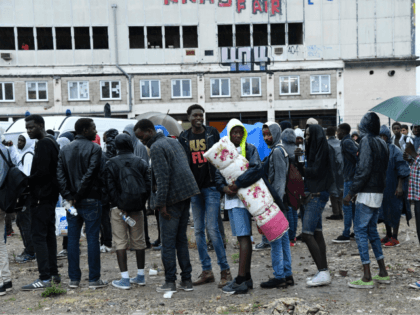 Migrants wait to board buses as police prepare the evacuation of a makeshift camp at Porte de la Chapelle, in the north of Paris, on August 18, 2017. More than a thousand migrants and refugees were evacuated on early August 18 from a makeshift camp that had been set up …