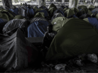 Burkina Faso's Aziz Porogo, a 28-year-old migrant, sits in his tent at a makeshift camp set under a bridge near Porte de la Villette, northern Paris on April 20, 2018. - Aziz left Burkina Faso in 2009 as he could not find a job in his impoverished home country. Like …
