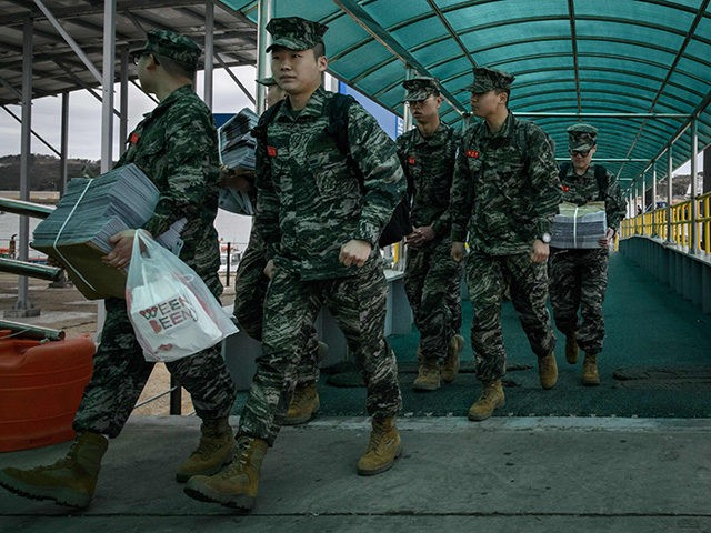 In a photo taken on April 24, 2018 South Korean soldiers disembark from a passenger ferry at Yeonpyeong island, near the 'northern limit line' sea boundary with North Korea. (Photo by Ed JONES / AFP) / To go with SKorea-NKorea-diplomacy-politics-attack, Focus by Sunghee Hwang (Photo credit should read ED JONES/AFP/Getty …