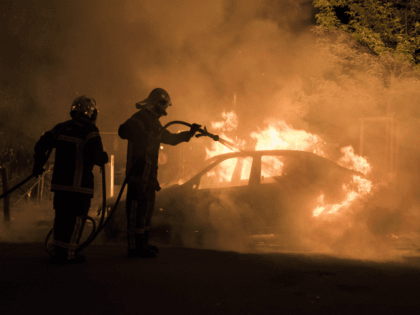 Firefighters work to put out a fire in a car in the Malakoff neighborhood of Nantes early on July 4, 2018. - Groups of young people clashed with police in the western French city of Nantes on the night of July 3 after a man was shot dead by an …