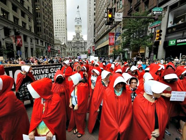 "Protesters, in view of City Hall, center, dressed as characters from ""The Handmaid's Tale,"" demonstrate against Vice President Mike Pence's visit to the Union League in Philadelphia, Monday, July 23, 2018."