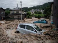 A picture shows cars trapped in the mud after floods in Saka, Hiroshima prefecture on July 8, 2018. - Japan's Prime Minister Shinzo Abe warned on July 8 of a 'race against time' to rescue flood victims as authorities issued new alerts over record rains that have killed at least …