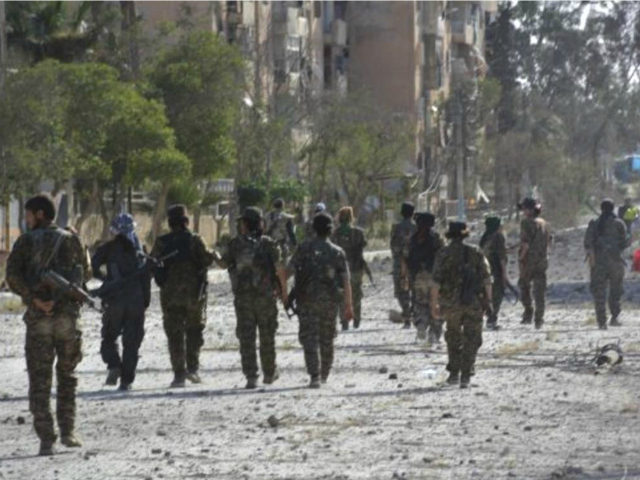 In this undated photo released Thursday, May 11, 2017, by Hawar News, the news agency for the semi-autonomous Kurdish areas in Syria, shows fighters from the Kurdish-led Syria Democratic Forces, patrolling on a street in Tabqa, northern Syria. Syrian Kurdish-led forces say they are carrying out mine-clearing operations at the …