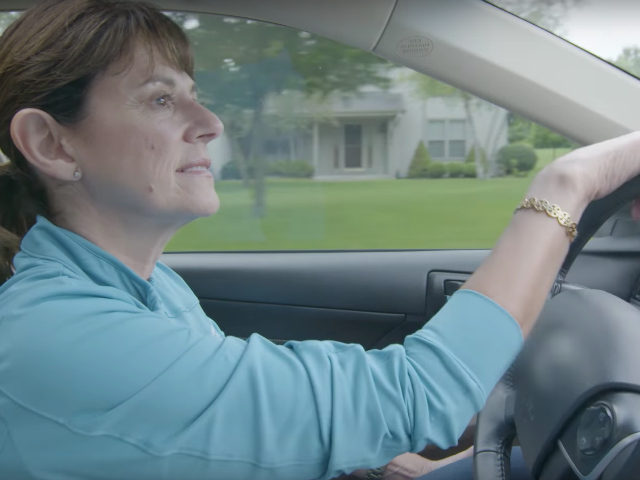 Leah Vukmir appears in a campaign ad driving a car with a blurred Toyota logo.