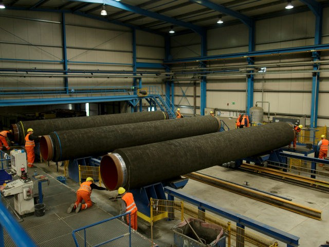 Workers are working on pipes in the production hall at the Nord Stream 2 facility at Mukran on Ruegen Islandon October 19, 2017 in Sassnitz, Germany. Nord Stream is laying a second pair of offshore pipelines in the Baltic Sea between Vyborg in Russia and Greifswald in Germany for the …