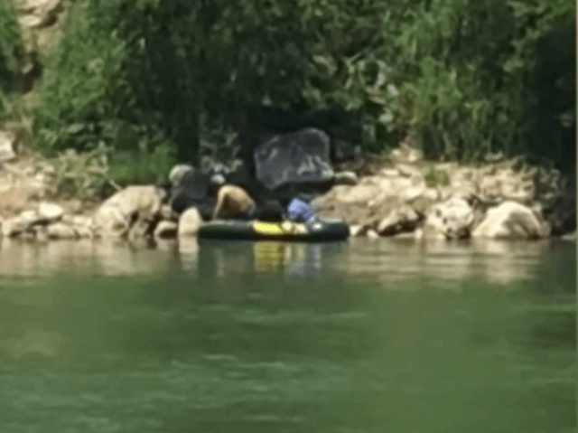 A human smuggler paddles two illegal immigrants across the Rio Grande River in front of a CBS News crew.
