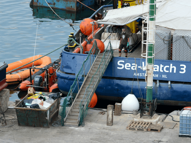 A crew member of the Dutch search and rescue vessel Sea Watch 3 (L), work as they lies berthed in a dock in the harbour of Marsa in Malta, undergoing repairs on June 24, 2018. (Photo by Matthew Mirabelli / AFP) (Photo credit should read MATTHEW MIRABELLI/AFP/Getty Images)