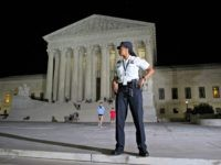 A Supreme Court Police officer stands watch as a protesters demonstrate in front of the Supreme Court in Washington, Monday, July 9, 2018, after President Donald Trump announced Judge Brett Kavanaugh as his Supreme Court nominee.