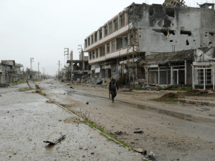 A fighter of Syrian pro-government forces walks past damaged buildings on a street in the town of Sheikh Miskeen in southern Daraa province on January 26, 2016 after the Syrian army and their allies retook the strategic town from rebel forces. Sheikh Miskeen lies on a vital crossroads between Damascus …