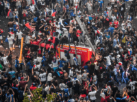 This picture taken from the terrace of the Publicis drugstore on July 15, 2018 shows people standing on a firefighter vehicle after France won the Russia 2018 World Cup final football match between against Croatia, on the Champs-Elysees avenue in Paris.