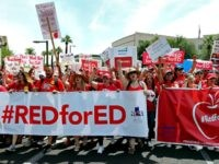 PHOENIX, AZ - APRIL 26: Arizona teachers march through downtown Phoenix on their way to the State Capitol as part of a rally for the #REDforED movement on April 26, 2018 in Phoenix, Arizona. Teachers state-wide staged a walkout strike on Thursday in support of better wages and state funding …
