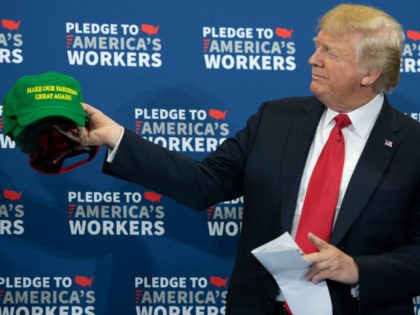 US President Donald Trump holds up 'Make Our Farmers Great Again!' hats as he arrives for a roundtable discussion on workforce development at Northeast Iowa Community College in Peosta, Iowa, July 26, 2018. (Photo by SAUL LOEB / AFP) (Photo credit should read SAUL LOEB/AFP/Getty Images)