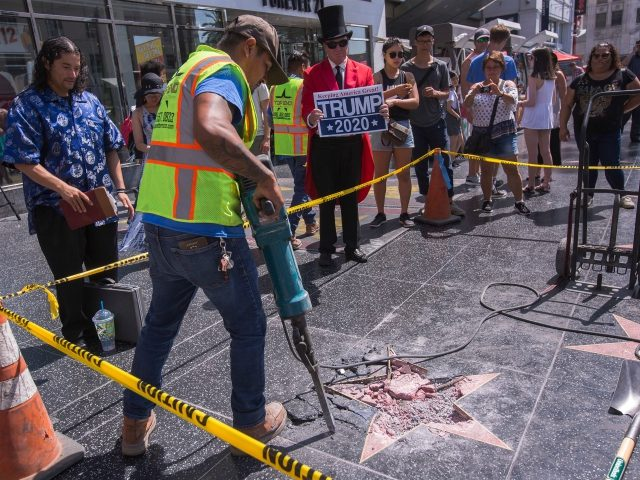 A worker removes the remains of the Star of US President Donald J. Trump on the Hollywood Walk of Fame after it was destroyed by a vandal in the early morning hours on July 25, 2018 in Los Angeles, California. (Photo by DAVID MCNEW / AFP) (Photo credit should read …