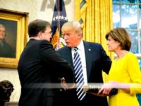 President Donald Trump, center, shakes hands with new Secretary of Veterans Affairs Robert Wilkie, left, following a ceremony in the Oval Office of the White House, Monday, July 30, 2018, in Washington. Also pictured is Wilkie's wife Julia, right.