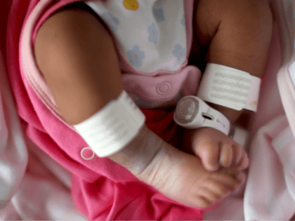 BIRMINGHAM, ENGLAND - JANUARY 22: Editors Note: This image may have been digitally manipulated for confidentiality to remove any patient identidy data. A newborn baby girl wears an electronic tag as she sleeps in her cot in the maternity unit of Birmingham Women's Hospital on January 22, 2015 in Birmingham, …