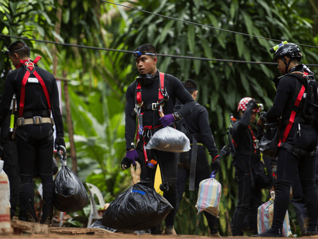 Thai divers carry supplies as rescue operations continue for 12 boys and their coach trapped at Tham Luang cave at Khun Nam Nang Non Forest Park in the Mae Sai district of Chiang Rai province on July 5, 2018. - Thai rescuers vowed to take a 'no risk' approach to …